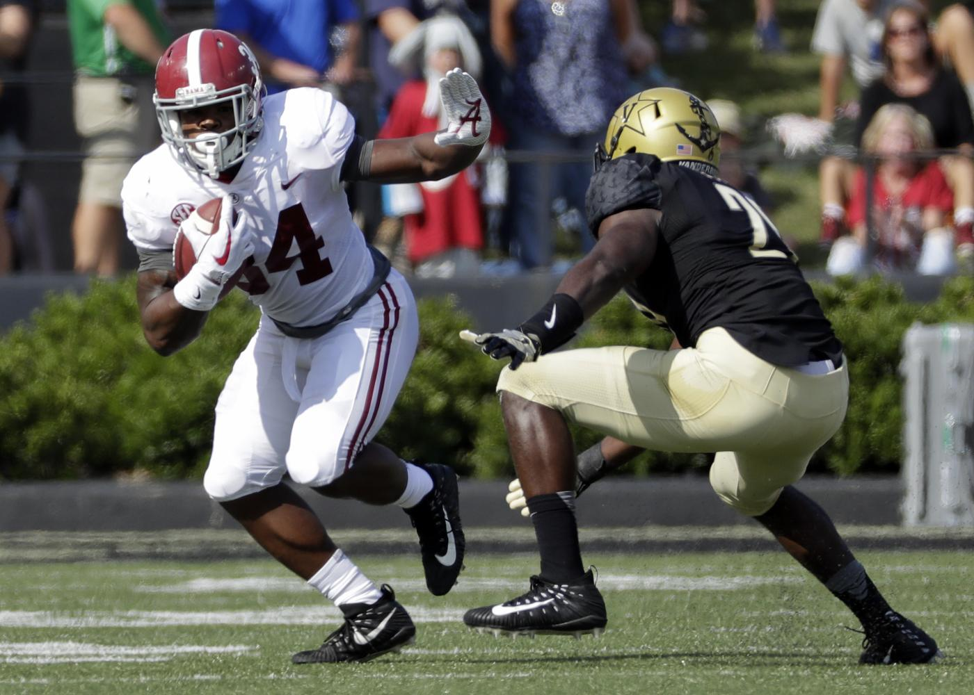 Alabama running back Damien Harris (34) runs past Vanderbilt linebacker Oren Burks (20) in the first half of an NCAA college football game Saturday, Sept. 23, 2017, in Nashville, Tenn. Harris ran for a career-high 151 yards and three touchdowns as top-ranked Alabama routed Vanderbilt 59-0 Saturday in the Southeastern Conference opener for both teams. (AP Photo/Mark Humphrey)