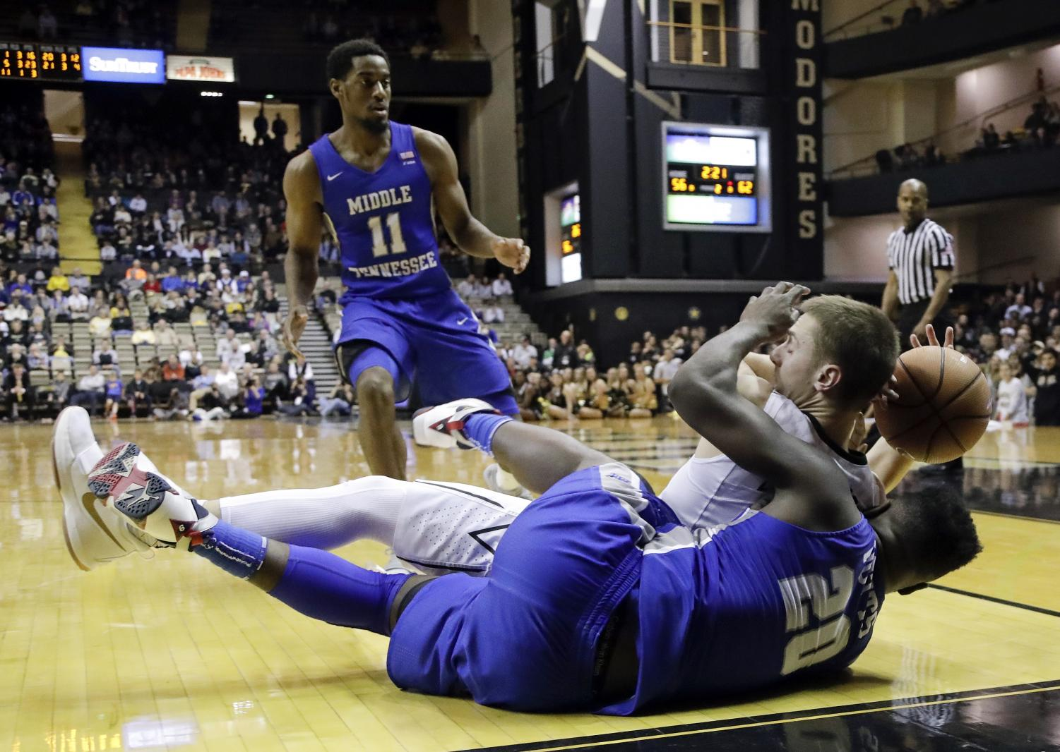 Middle Tennessee guard Giddy Potts (20) dives for the ball with Vanderbilt guard Riley LaChance in the second half of an NCAA college basketball game Wednesday, Dec. 6, 2017, in Nashville, Tenn. Middle Tennessee guard Edward Simpson (11) watches. Middle Tennessee won 66-63. (AP Photo/Mark Humphrey)