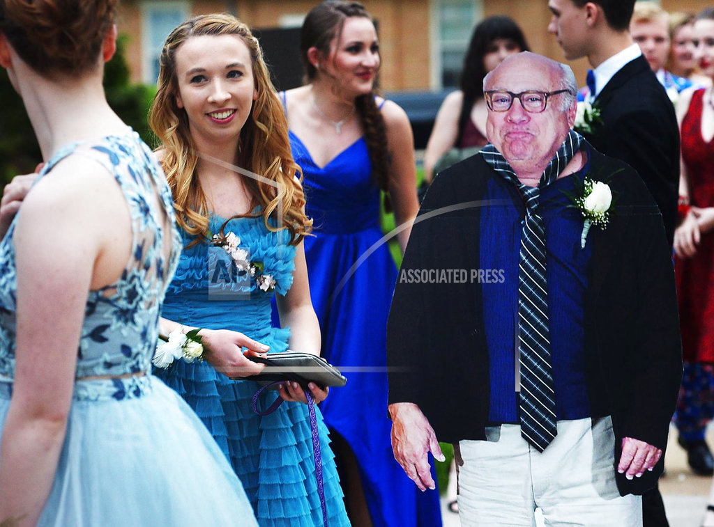 Allison Closs arrives for the Carlisle High School senior prom at Letort View Community Center at Carlisle Barracks in Carlise, Pa., on Friday, May 11, 2018, with a cutout of actor Danny DeVito. Closs and her famous two-dimensional date joined other Carlisle High School seniors Friday for prom. Closs purchased the cutout of DeVito online along with a scooter she used to move the figure with.   (Michael Bupp /The Sentinel via AP)