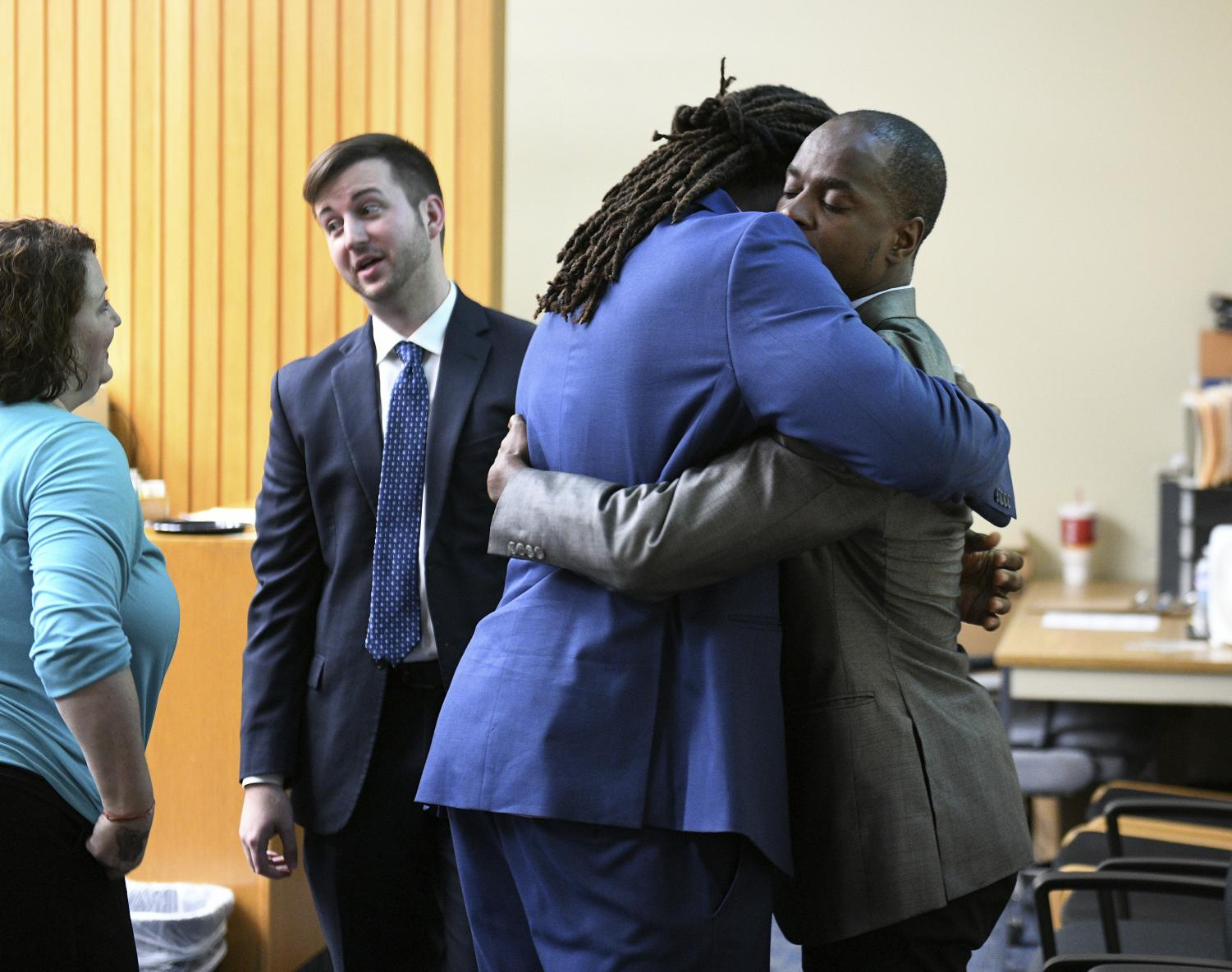 A.J. Johnson, left, and Michael Williams hug after a jury acquitted them of aggravated rape charges Friday, July 27, 2018, in Knoxville, Tenn. Johnson and Williams were indicted on February 2015 after a woman said both men raped her during a party at Johnson's apartment in the early morning hours of Nov. 16, 2014. Johnson and Williams were suspended from the Tennessee football team less than 48 hours after the party and never played for Tennessee again. (Michael Patrick/Knoxville News Sentinel via AP)