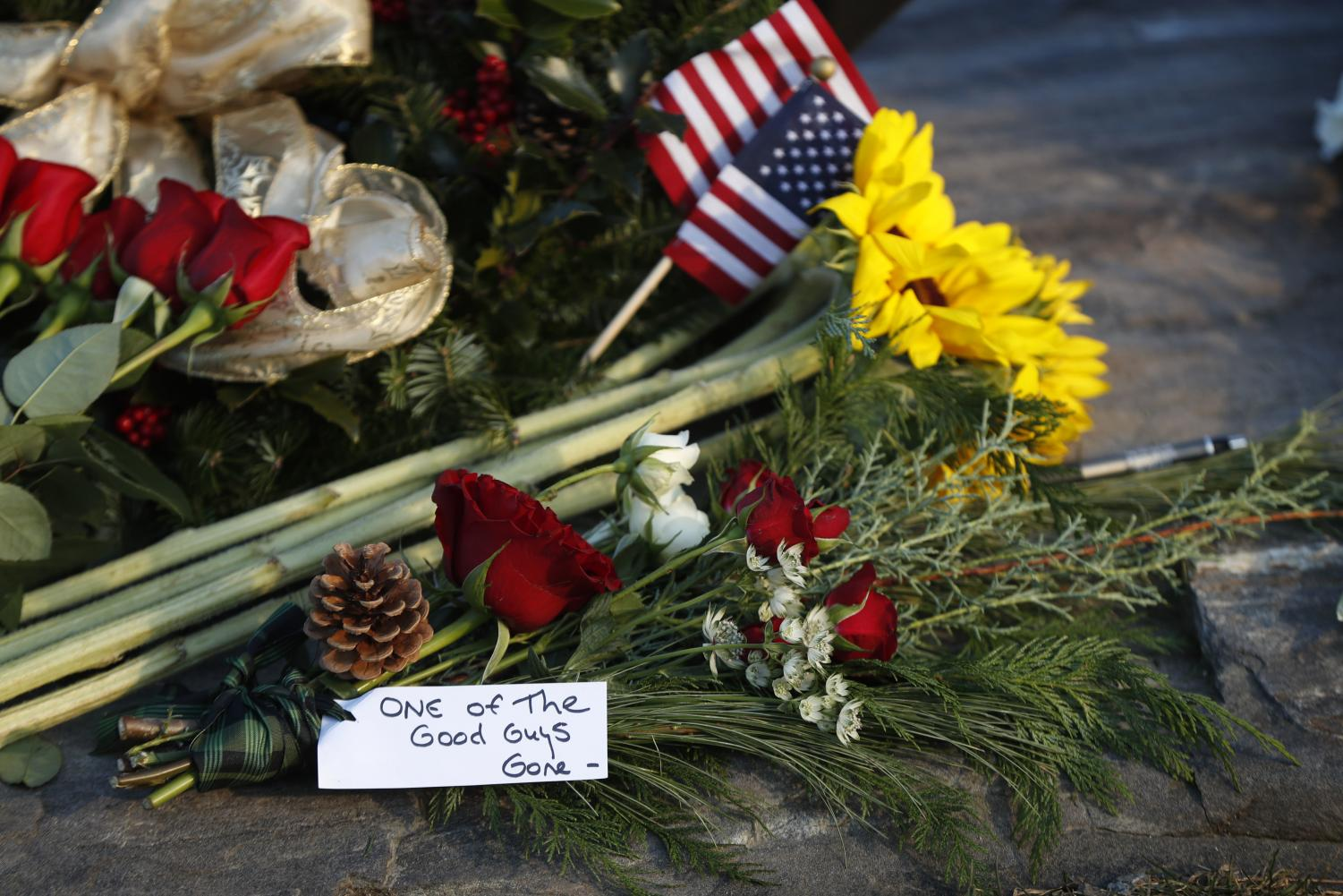 Flowers and a note saying former President George H. W. Bush was