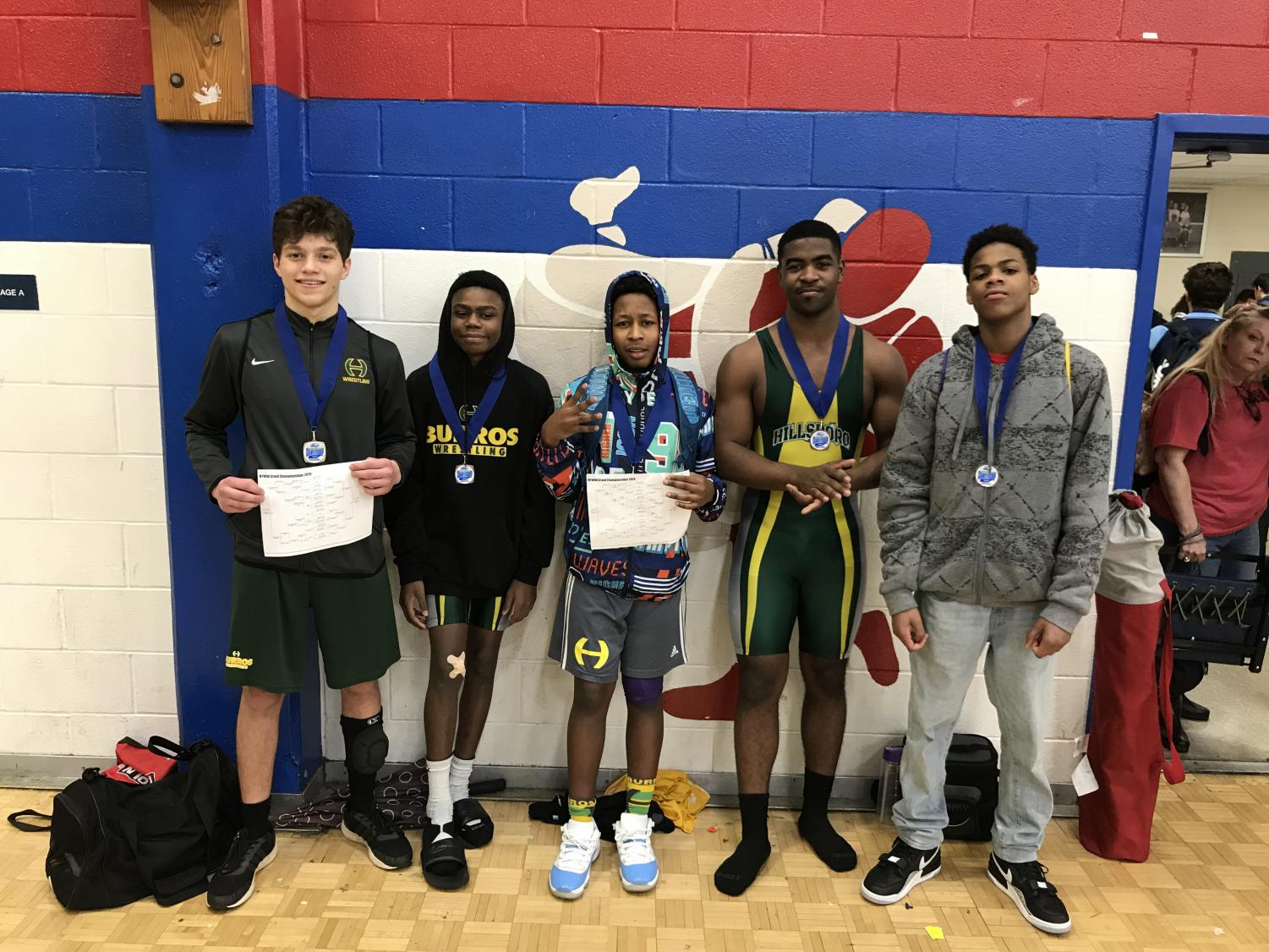 L-R Wrestlers Cooper Sacks (1st place), Christian Brown (3rd); Tahj Jackson (1st); Maikel Holloway 2nd) at the MTWOA Grand Championship Wrestling tournament for Freshmen, Women and JV.