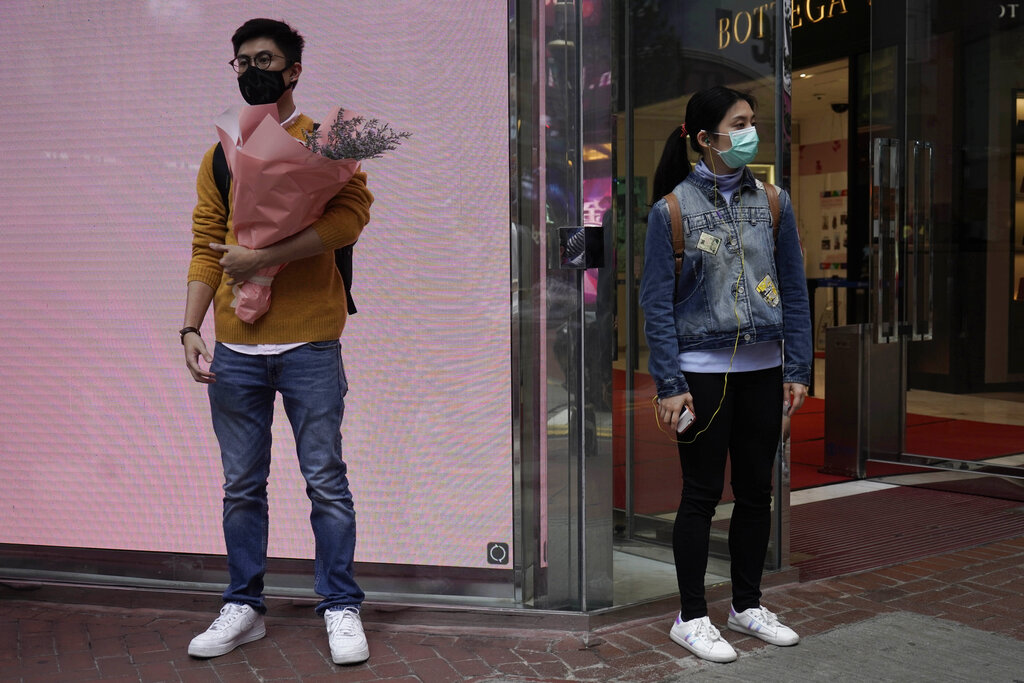 A+man+wearing+protective+face+mask+waits+at+a+street+corner+with+a+bouquet+on+Valentine%27s+Day+in+Hong+Kong%2C+Friday%2C+Feb.+14%2C+2020.+China+on+Friday+reported+another+sharp+rise+in+the+number+of+people+infected+with+a+new+virus%2C+as+the+death+toll+neared+1%2C400.+%28AP+Photo%2FKin+Cheung%29