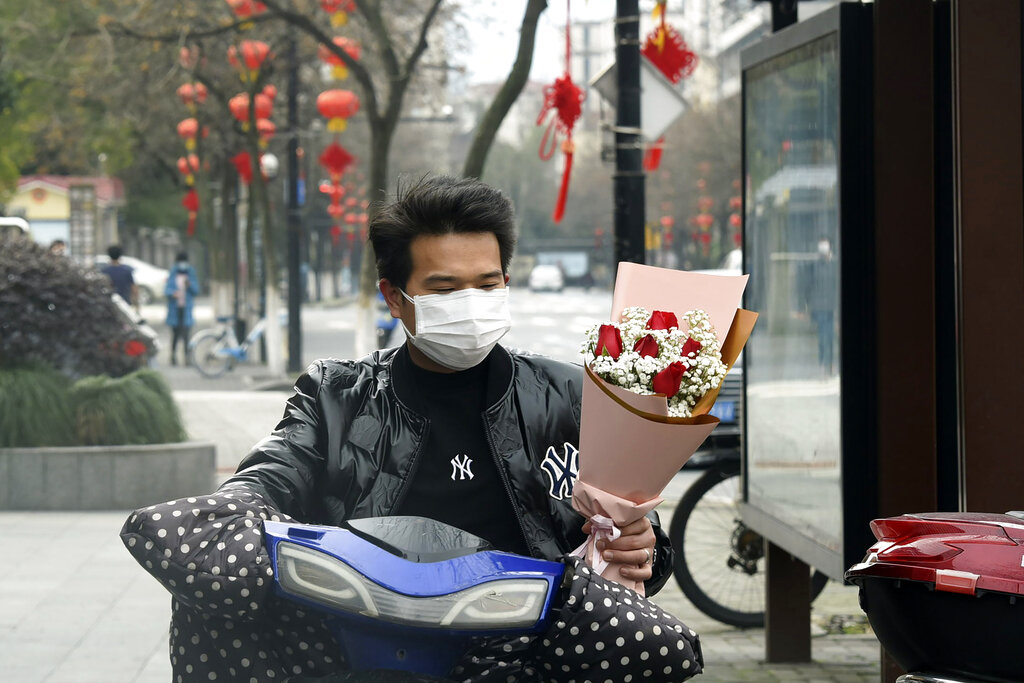 A+man+wearing+a+face+mask+carries+a+Valentine%27s+Day+bouquet+as+he+rides+a+scooter+in+Hangzhou+in+eastern+China%27s+Zhejiang+Province%2C+Friday%2C+Feb.+14%2C+2020.+China+on+Friday+reported+another+sharp+rise+in+the+number+of+people+infected+with+a+new+virus%2C+as+the+death+toll+neared+1%2C400.+%28Chinatopix+via+AP%29