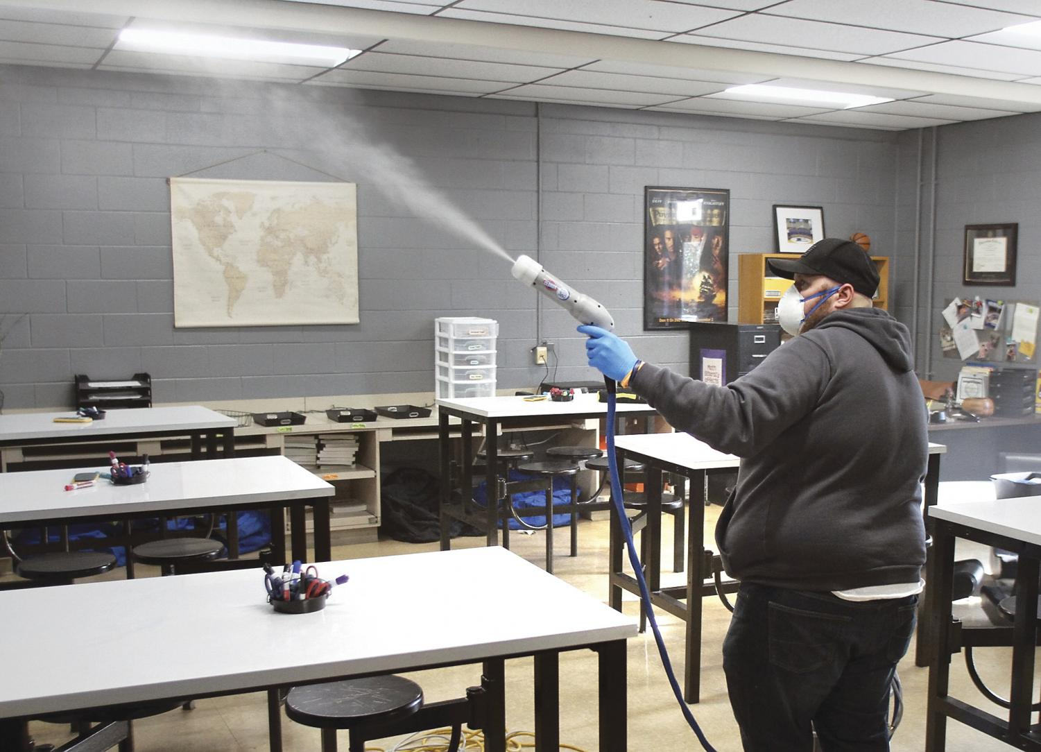 In this Wednesday, Jan. 22, 2020 photo, head custodian Bubba McKenzie uses the Clorox Total 360 System to sanitize a classroom at Eagleton Middle School in Maryville, Tenn. The electrostatics sprayer creates a fine mist that reaches more surfaces faster than traditional cleaning. Blount County Schools have four of the machines for its 21 schools. (Tom Sherlin/The Daily Times via AP)
